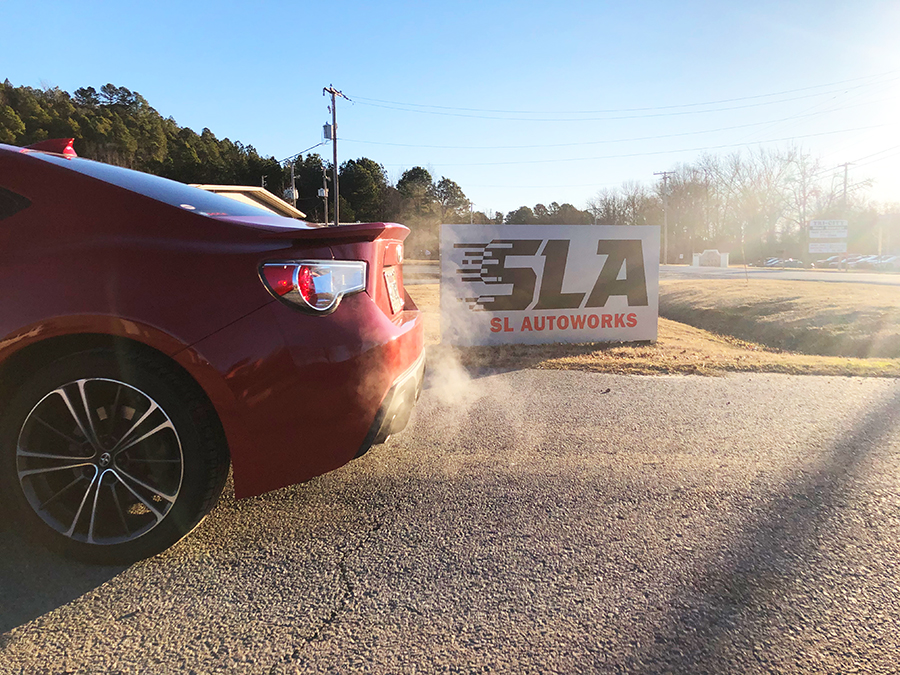 Red Scion in front of SL Autoworks sign Maumelle