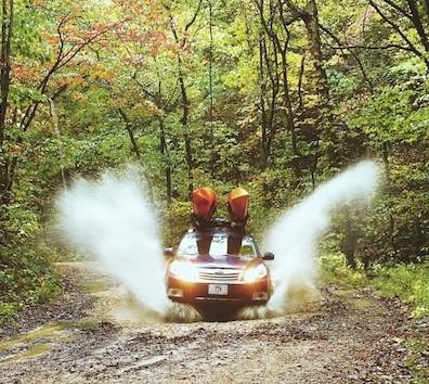 Subaru woods splashing puddle