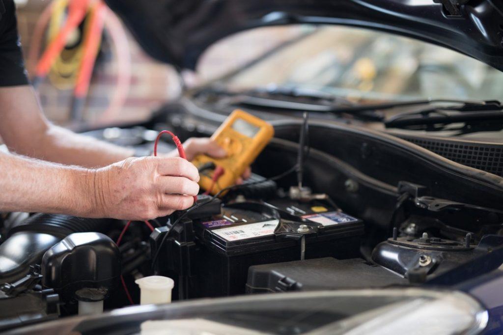 mechanic testing car battery SL Autoworks
